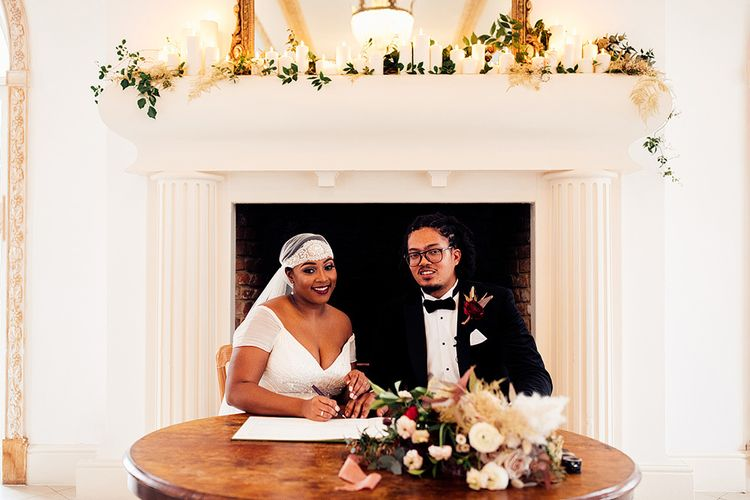 Black Bride in Juliet Cap Veil and Eliza Jane Howell Wedding Dress and Groom in Tuxedo Signing the Register