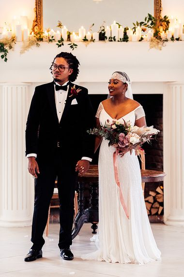 Black Bride in Juliet Cap Veil and Eliza Jane Howell Wedding Dress and Groom in Tuxedo Standing at the Altar