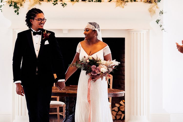 Black Bride in Juliet Cap Veil and Eliza Jane Howell Wedding Dress and Groom in Tuxedo Holding Hands  at the Altar