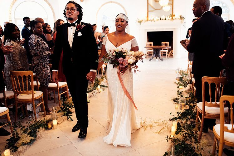 Black Bride in Juliet Cap Veil and Eliza Jane Howell Wedding Dress and Groom in Tuxedo Walking Up The Aisle as Husband and Wife
