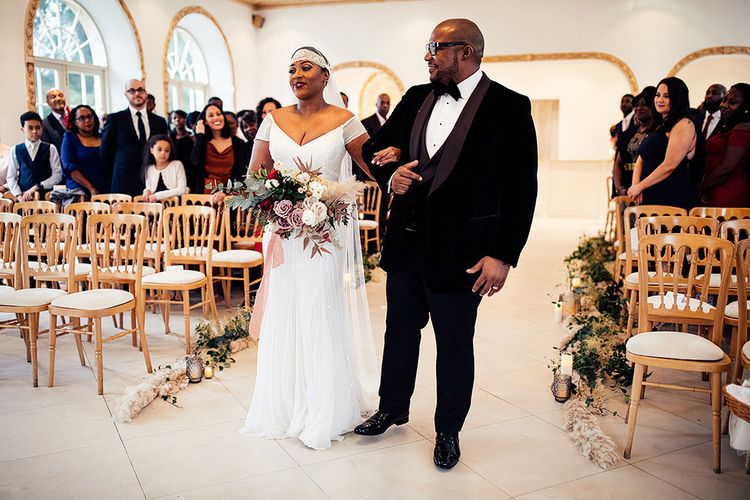 Black Bride in Juliet Cap Veil and Eliza Jane Howell Wedding Dress Walking Down the Aisle with Her Dad in a Tuxedo