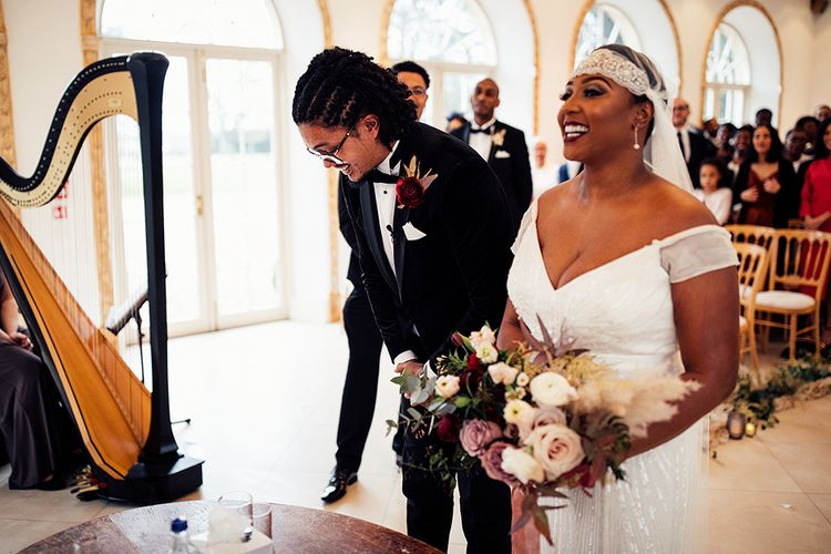 Black Bride in Juliet Cap Veil and Eliza Jane Howell Wedding Dress Meeting Her Groom at the Altar in a Tuxedo