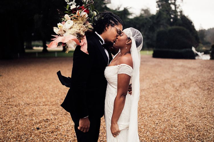 Black Bride in Juliet Cap Veil and Eliza Jane Howell Wedding Dress and Groom in Tuxedo Kissing