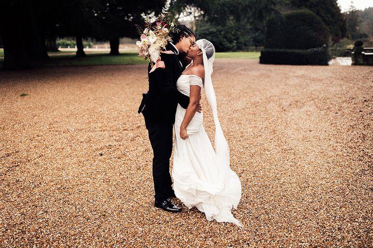Black Bride in Juliet Cap Veil and Eliza Jane Howell Wedding Dress and Groom in Tuxedo Embracing