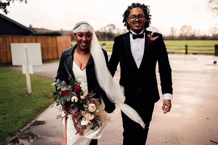 Black Bride in Juliet Cap Veil, Eliza Jane Howell Wedding Dress and Leather Jacket and Groom in Tuxedo and Glasses Holding Hands