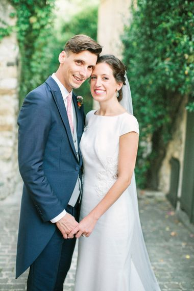 Bride in Rime Arodaky Wedding Dress and Groom in Traditional Morning Suit Holding Hands