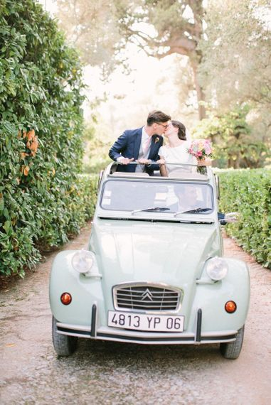 Bride in Rime Arodaky Wedding Dress and Groom in Traditional Morning Suit Travelling in  Convertible VW Beetle
