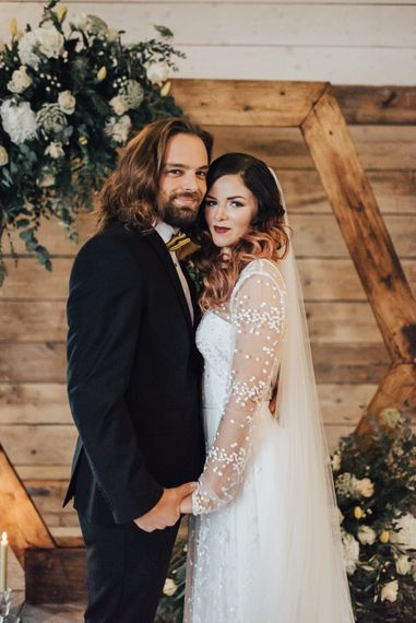 Boho Bride & Long Haired Groom in Front of Hexagonal Moon Gate | Geometric Wedding Decor & Styling by Locate to Create at The Cherry Barn | Rebecca Carpenter Photography