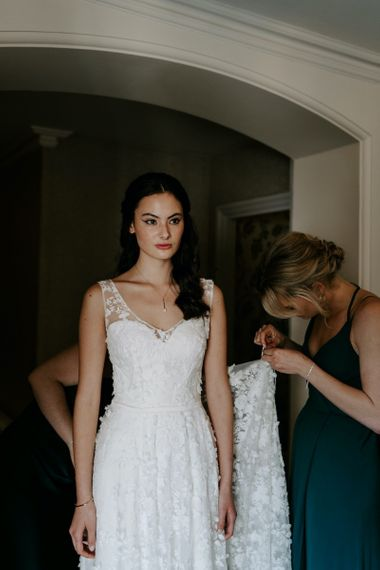 Bride with sweetheart neckline dress with lace overlay with emerald green bridesmaid dresses