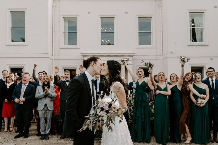 Bride and groom kiss in front of  guests and  bridesmaids wearing emerald green bridesmaid dresses