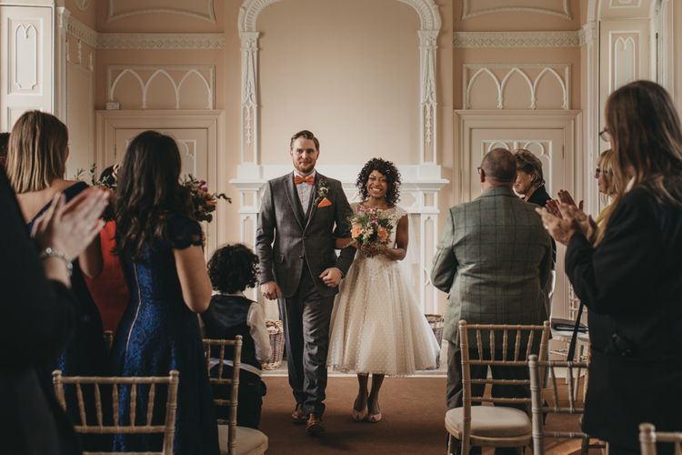 Bride in Polka Dot Tulle Short Wedding Dress  and Groom in Grey Check Suit Walking up the Aisle Just Married