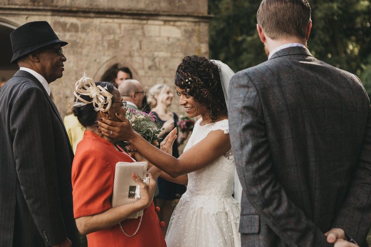 Bride in Polka Dot Wedding Dress with Curly Hair Greeting Wedding Guests