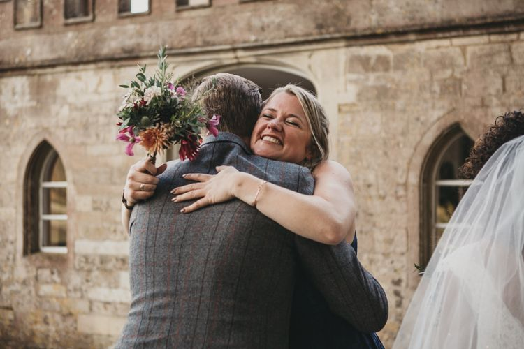 Bridesmaid Hugging the Groom in Grey Check Suit