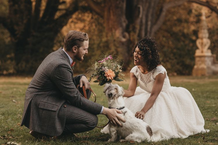 Bride in Polka Dot Tea Length Wedding Dress and Groom in Grey Check Suit with their Pet Dog