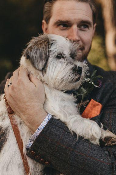 Groom in Grey Check Suit Hugging His Pet Dog