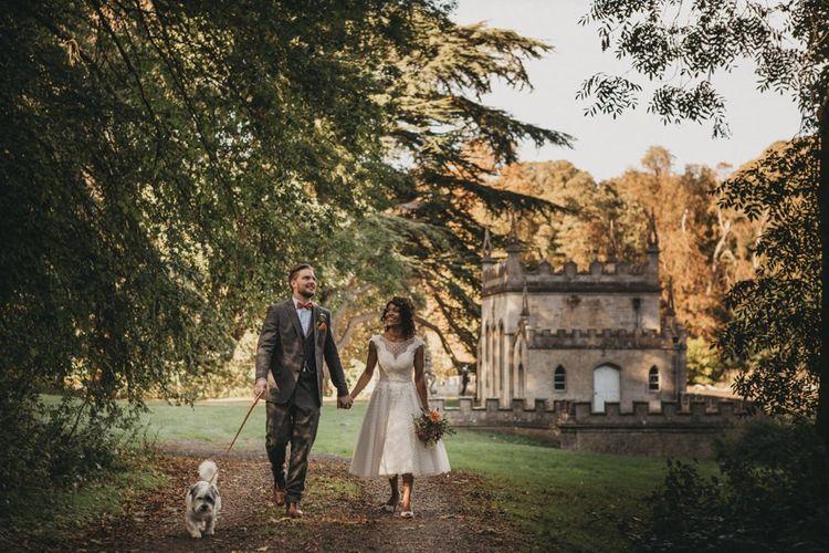 Bride in Polka Dot Tea Length Wedding Dress and Groom in Grey Check Suit Walking their Pet Dog