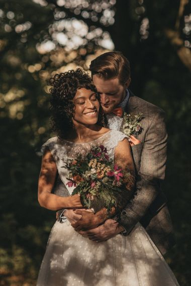 Groom in Grey Check Suit Embracing His Bride Holding a Wildflower Wedding Bouquet
