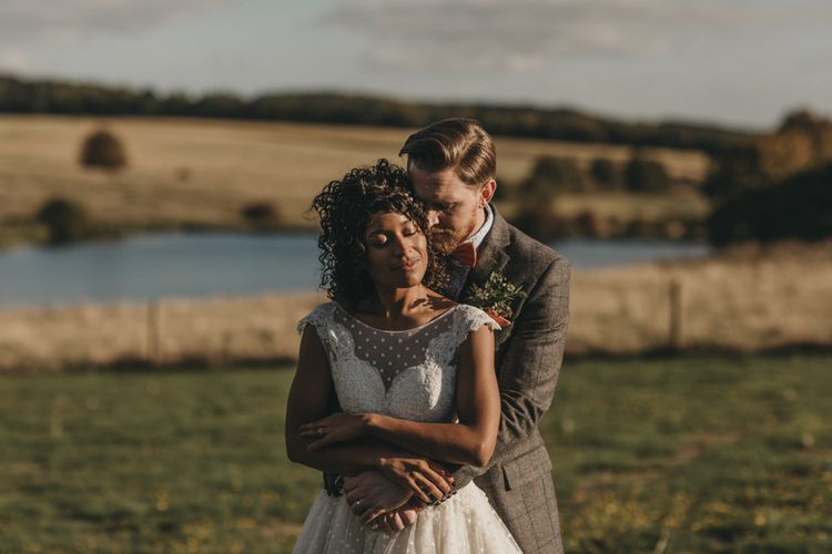 Groom in Grey Check Suit Embracing His Bride  in a Tulle Tea Length Wedding Dress
