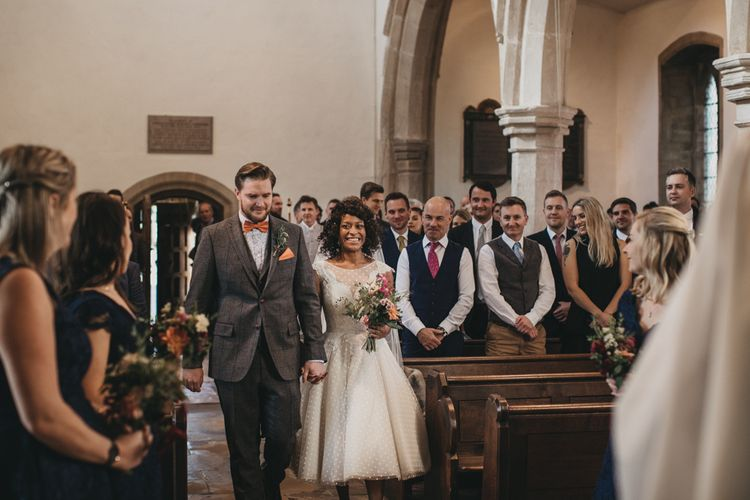 Church Wedding Ceremony with Bride in Tea Length Wedding Dress and Groom in Wool Suit Walking Up the Aisle