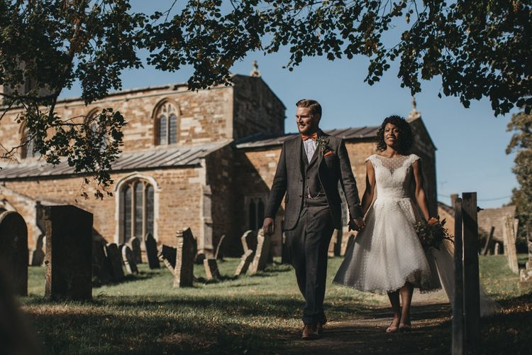 Bride in Polka Dot Tulle Wedding Dress and Groom in Grey Wool Suit Walking Through the Church Courtyard