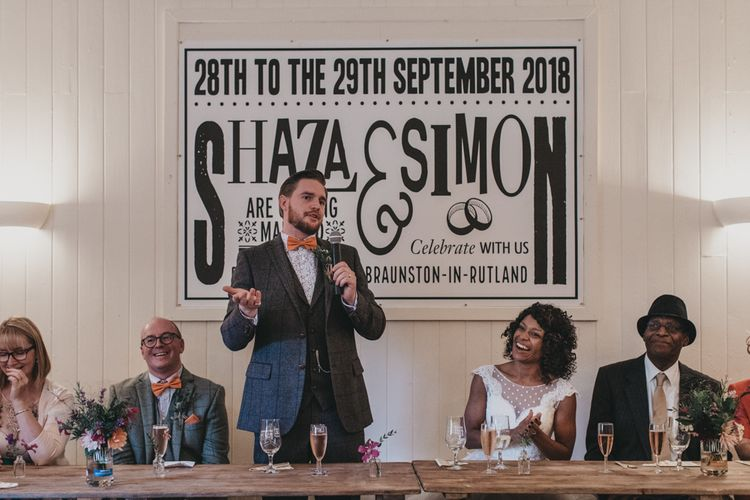 Groom in Grey Check Suit Delivering His Wedding Speech with Top Table Back drop Poster
