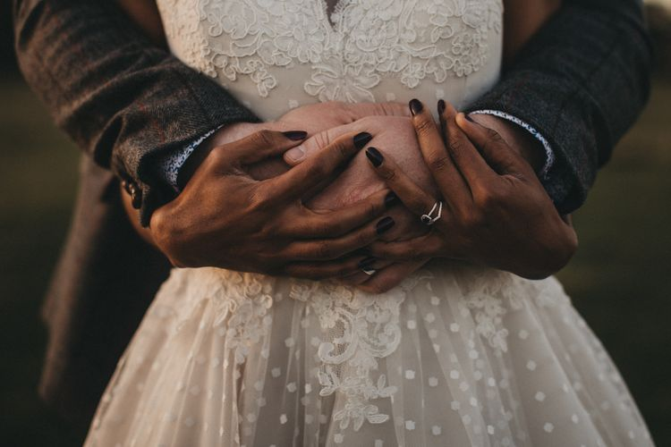 Groom Embracing His Bride in a Polka Dot and Lace Tulle Wedding Dress