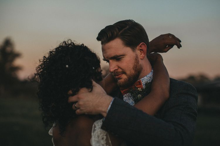 Groom in Floral Shirt and Bow Tie Embracing His Bride with Curly Hair