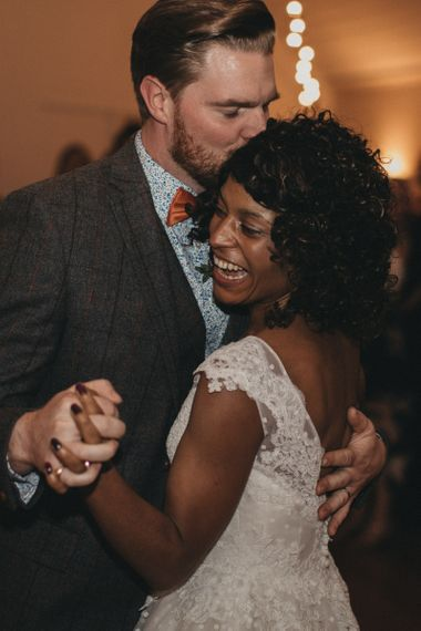 Groom in Wool Suit, Floral Shirt and Bow Tie Kissing His Brides Head During the First Dance