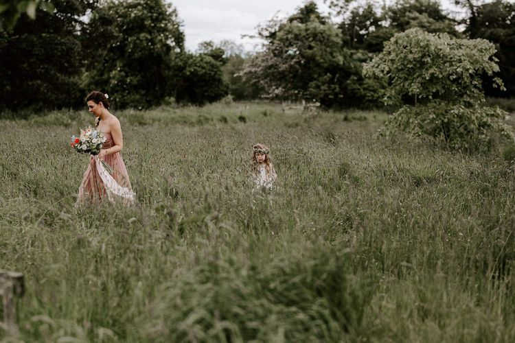 Bridesmaid and flower girl make their way to outdoor ceremony