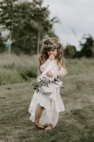 Beautiful flower girl in white dress with flower crown