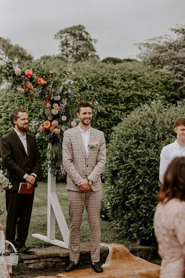 Groom sees bride walking down the aisle during outdoor ceremony