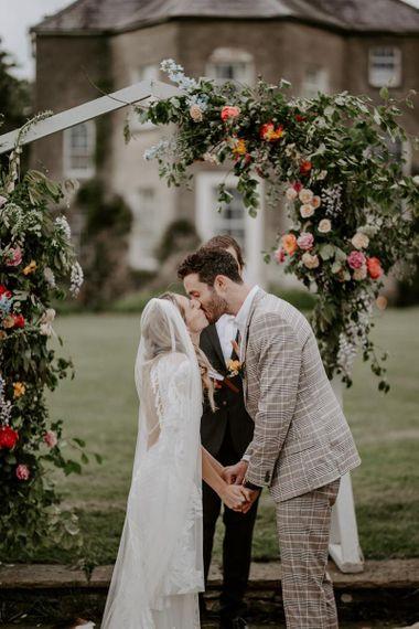 Coral wedding flower arch at micro wedding