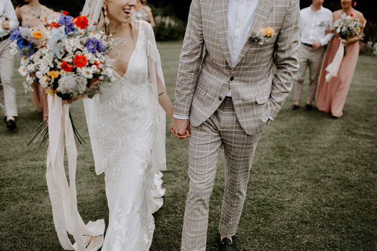 Cream wedding suit for groom at micro wedding with bride carrying wildflower bouquet