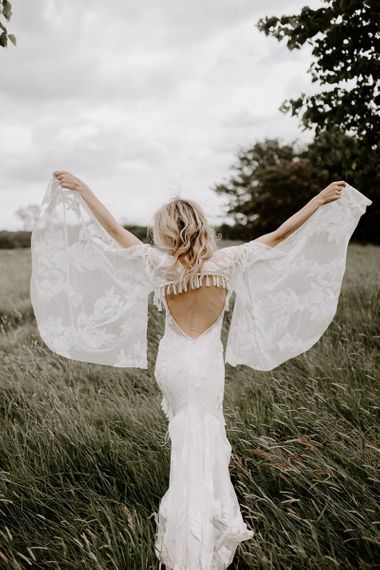 Batwing wedding dress with open back and fringe detail