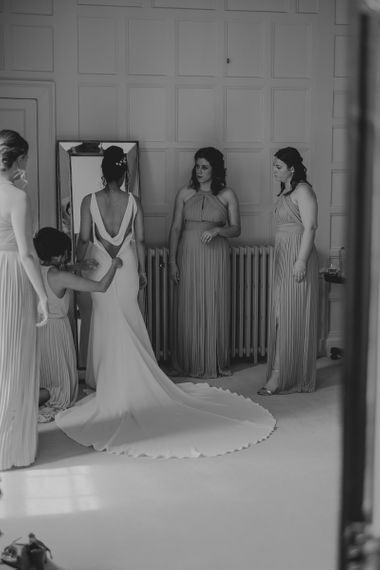 Wedding Morning Bridal Preparations with Bridesmaids Helping the Bride into Her Pronovias Fitted Wedding Dress