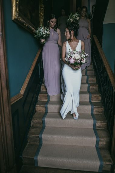 Bride Walking Down the Stairs in a Pronovias Wedding Dress with Her Bridesmaids