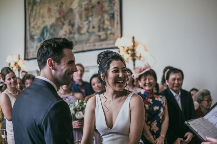Wedding Ceremony with Bride with High Bun Laughing at the Altar