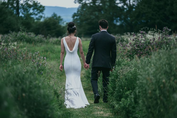 Bride in Fitted Pronovias Wedding Dress with Back Buttons and Cowl Detail and Groom in Cad & The Dandy Suit