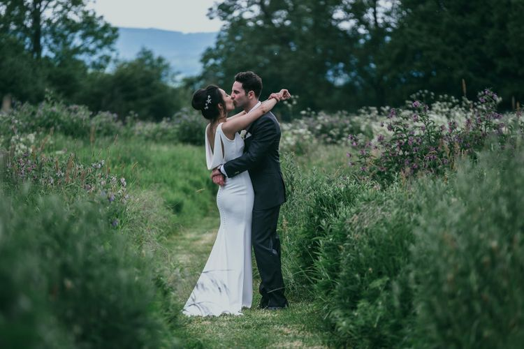 Bride in Fitted Pronovias Wedding Dress with Cowl Back Detail and Groom in Cad & The Dandy Suit Embracing