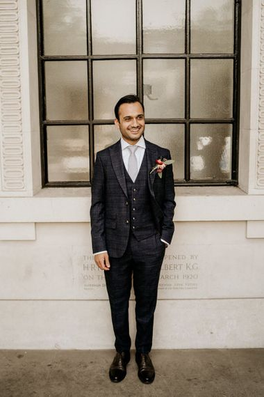 Groom in navy check wedding suit