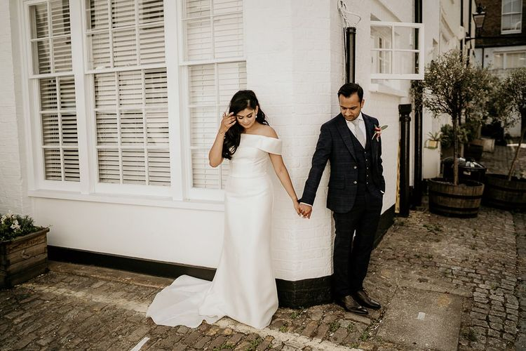 Bride and groom holding hands around a corner