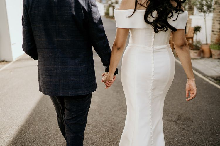 Groom in navy check suit and bride in off the shoulder wedding dress with buttons down the back