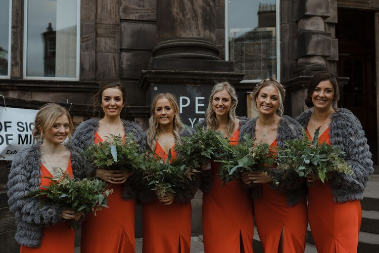 Bridesmaids in Burnt Orange Dresses with Charcoal Grey Loop Cardigans  and Greenery Bouquets
