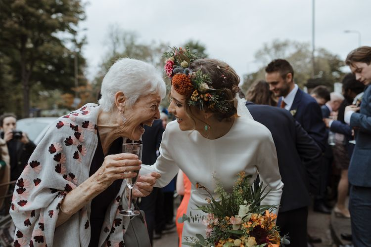 Bride in Satin Wedding Dress with Autumnal Flower Crown Talking to Wedding Guest