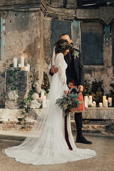 Bride in Bohemian Rue De Seine Wedding Dress and Groom in Red Tartan Kilt  Embracing at The Asylum Altar