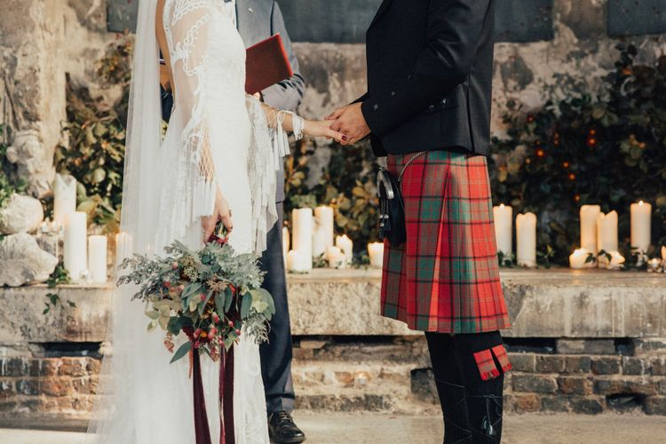 Bride in Bohemian Rue De Seine Wedding Dress and Groom in Red Tartan Kilt Holding Hands During The Wedding Ceremony