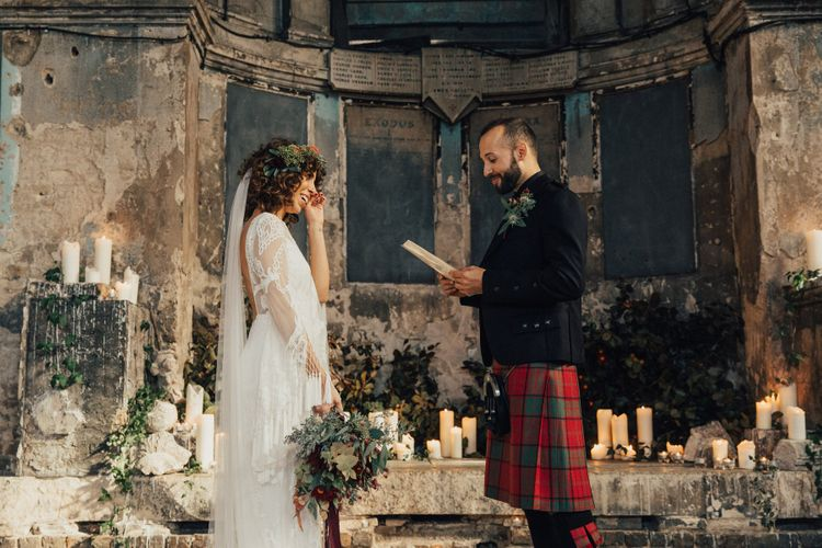 Emotional Bride in a Boho Rue De Seine Wedding Dress Wiping Her Tears as Her Groom in Red Tartan Kilt Reads His Wedding Vows