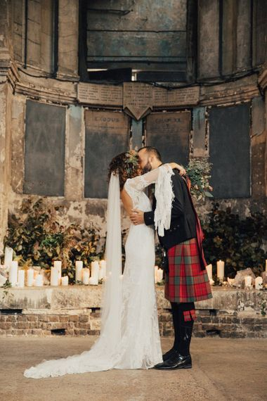 Bride in a Boho Rue De Seine Wedding Dress and Groom in Red Tartan Kilt Kissing After Their Wedding Ceremony