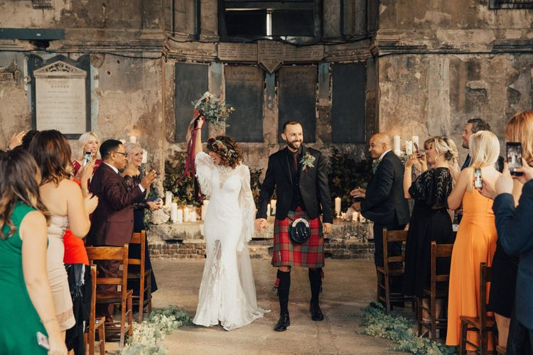 Bride in a Boho Rue De Seine Wedding Dress and Groom in Red Tartan Kilt  just Married Walking up the Aisle