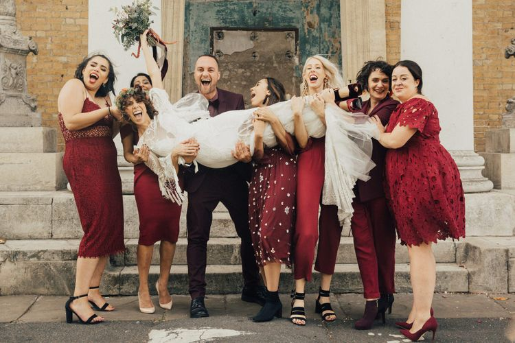 Bridal Party in Different High Street Burgundy Outfits Holding the Bride in a Rue De Seine Boho Wedding Dress